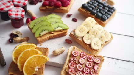 kızılcık : Assortment of healthy fresh breakfast toasts. Bread slices with peanut butter and various fruits and ingredients on side. Placed on white wooden table. Top view, with copy space.