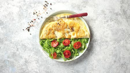 omlet : Classic egg omelette served with cherry tomato and arugula salad on side. Placed on white ceramic plate. Stone background with copy space. Stok Video