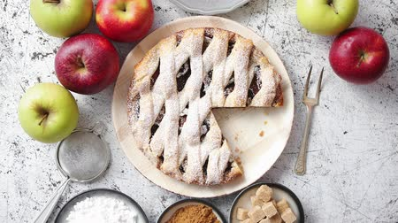 american cuisine : Fresh baked apple pie with cutted slice on small plate. With ingrediends on side. Fresh fruits, brown sugar cubes, cinnamon. Sprinkled with powder sugar. Stock Footage