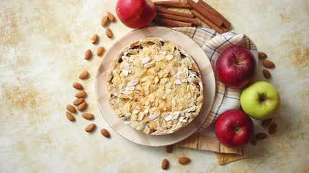 desery : Freshly baked homemade apple pie with almond flakes cake on yellow rusty background. Fresh apple fruits, cinnamon sticks and icing sugar. Top view with copy space.