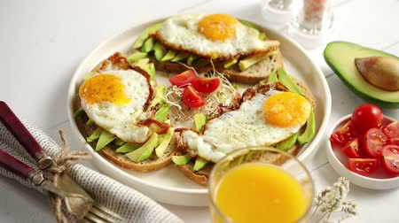 peper : Delicious healthy breakfast with sliced avocado sandwiches with fried egg on top of bread. With orange juice, cherry tomatoes, radish sprouts, salt and peper. Flat lay, top view. Stock Footage