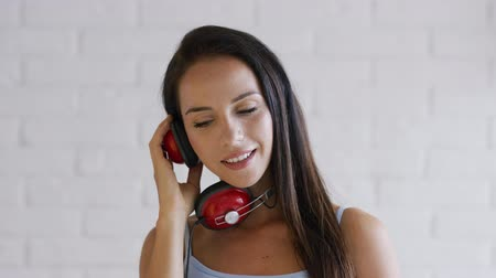 dişlek : Attractive young lady with brown hair and modern headphones cheerfully smiling and looking at camera while standing on white background Stok Video