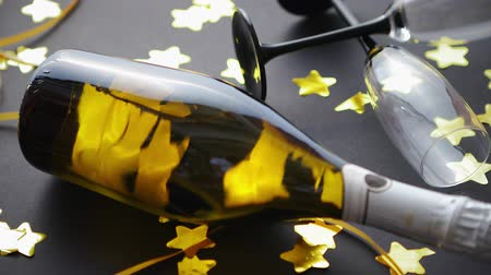 serpentine : Glasses and bottle of champagne with golden serpentines and confetti lying on black background. New Year or party celebration concept. Top view. Flat lay.