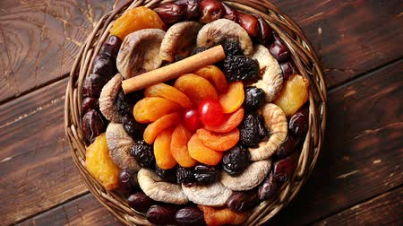 абрикосы : Mix of dried fruits in a small wicker basket on wooden table. Assortment contais apricots, plums, figs, dates, cherries, peaches. Above view with copy space.