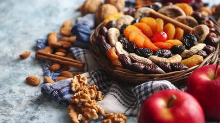 skořice : Composition of dried fruits and nuts in small wicker bowl placed on a stone table. Assortment contais almonds, walnuts, apricots, plums, figs, dates, cherries, peaches. Above view with copy space.