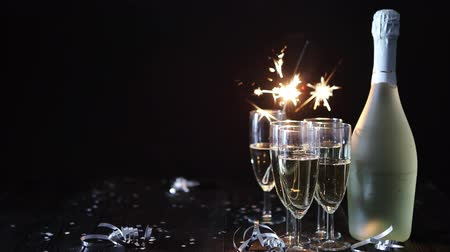 champagne bottles : Party composition image. Glasses filled with champagne placed on black table. With bottle of wine and sparkler. Elegant composition with copy space.