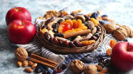 vime : Composition of dried fruits and nuts in small wicker bowl placed on a stone table. Assortment contais almonds, walnuts, apricots, plums, figs, dates, cherries, peaches. Above view with copy space.