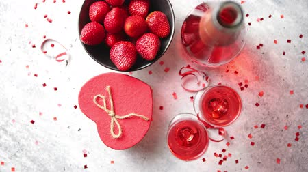 аперитив : Bottle of rose champagne, two glasses with fresh ripe strawberries and heart shaped boxed gift, placed on stone table for a special romantic occasion or Valentines. With copy space Стоковые видеозаписи