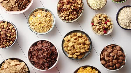 сортированный : Assortment of different kinds cereals placed in ceramic bowls with cornflakes, granola, cereals and oatmeal. The concept of breakfast food. Flat lay, top view on white wooden table.