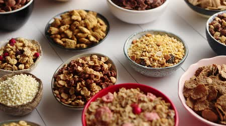 oat flakes : Assortment of different kinds cereals placed in ceramic bowls with cornflakes, granola, cereals and oatmeal. The concept of breakfast food. Flat lay, top view on white wooden table.