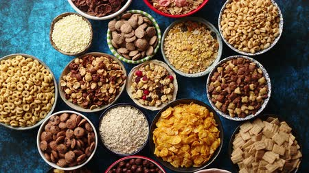 paslanmış : Assortment of various kinds cereals placed in ceramic bowls with cornflakes, granola, cereals and oatmeal. Flat lay, top view on blue rusty table with copy space in the middle Stok Video
