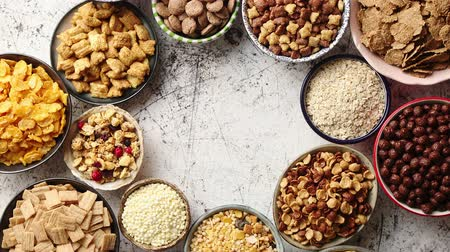oat flakes : Assortment of various kinds cereals placed in ceramic bowls with cornflakes, granola, cereals and oatmeal. Flat lay, top view on white rusty table with copy space in the middle Stock Footage