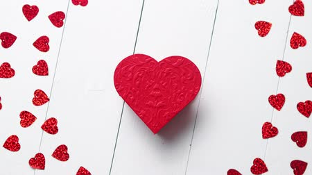 valentine : Valentines Day decoration composition. Heart shaped red sequins placed on white wooden table. Frame with copy space with heart in the middle. Romantic background. Flat lay, top view. Stock Footage
