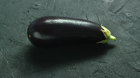 продуктовый : Closeup of single ripe eggplant with water drops on surface lying on gray background