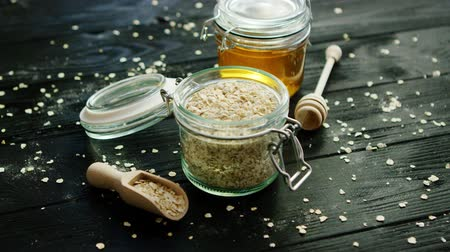 migalhas : From above view of oat in glass jar placed on wooden background with bowl of honey near Stock Footage