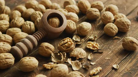 walnut shell : Closeup shot of fresh walnuts and wooden tool for cracking nuts lying on lumber tabletop Stock Footage