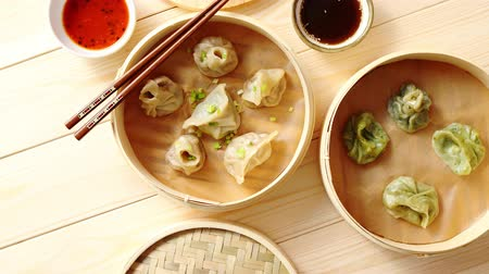 bamboo steamer : Traditional chinese dumplings served in the wooden bamboo steamer over raw wooden background table. Top View composition. Stock Footage