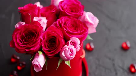 recipiente : Pink roses bouquet packed in red box and placed on black stone background with copy space. Valentines day or Romantic concept. Stock Footage