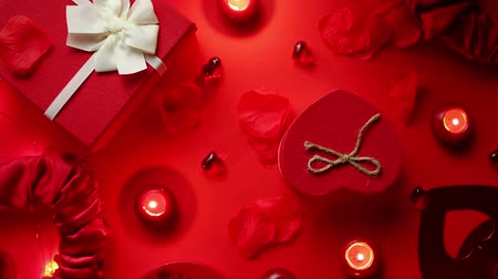 kerzenständer : Valentines day romantic decoration with roses, boxed gifts, candles, on a red background table. Top view, copy space.