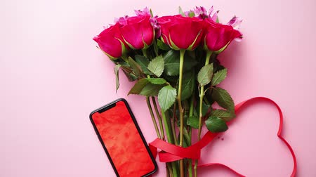şeklinde : Pink roses bouquet with hart shaped bow and mobile phone with copy space screen. Placed over pink table background. Top view shot. Stok Video