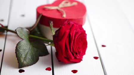 şeklinde : Single fresh red rose flower on the white wooden table with heart shaped sequins sprinkled around, candles and gift in box. Valentines or love concept. With copy space.