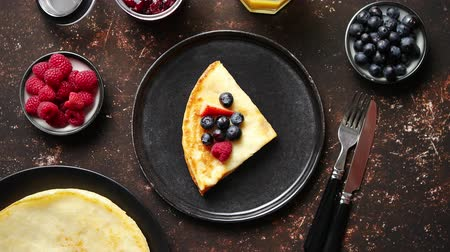 nalesniki : Tasety homemade pancake on black ceramic plate. Placed on dark rusty table. With fresh fruits, orange juice and marmalade. Top view, Flat lay.