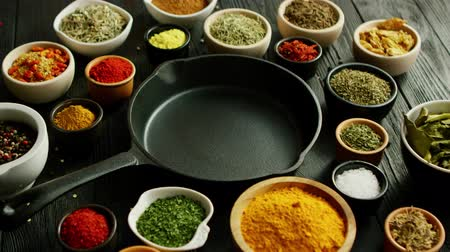 natural spicy : From above view of bowls with colorful spices and black pan placed in middle Stock Footage
