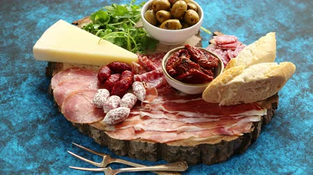antipasti : Delicious mix of different snacks and appetizers. Spanish tapas or italian antipasti on a wooden plate. View from above. Placed on blue table. Stock Footage
