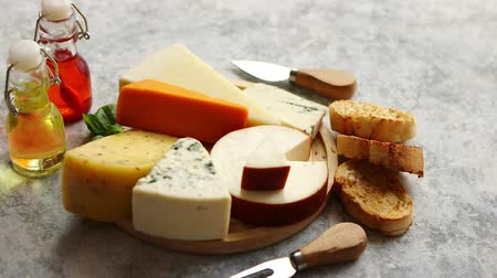typ : Various types of cheese served on rustic wooden board. Placed on concrete background. Dostupné videozáznamy