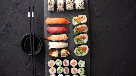 slate : Sushi rolls set with salmon and tuna fish served on black stone board. Top view of traditional japanese cuisine. Asian food on black stone slate with chopsticks.