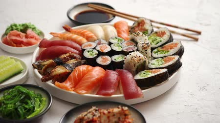 васаби : Asian food assortment. Various sushi rolls placed on round ceramic plate. Kimchi and goma wakame salads, fresh cucomber, ginger and wasabi. Soy souce and chopsticks on sides.