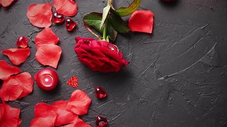 floral composition : Love and Valentines day concept. Red rose, petals, candles, dating accessories, boxed gifts, hearts, sequins on black stone background, frame composition, top view. Layout for greeting card