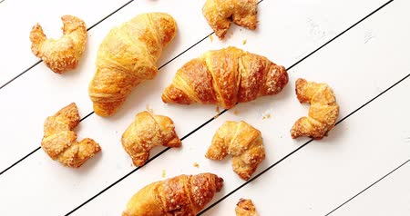 migalhas : From above shot of set of yummy fresh croissants of assorted sizes lying on surface of white timber tabletop