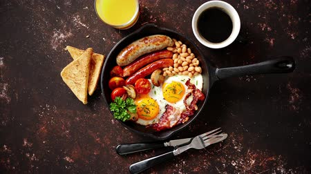 fried egg : English breakfast in iron cooking pan with fried eggs, sausages, bacon, beaked beans, toasts, orange juice and black coffee on dark rusty background.
