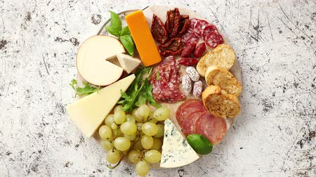 kiełbasa : Assortment of spanish tapas or italian antipasti with meat, ham, olives, cheese, nuts and bread placed on a white rusty table. Top view flat lay with copy space background