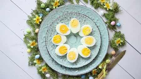 obrus : Easter table setting with flowers and eggs. Decorative ceramic plates with boiled eggs halfs. Rustical dishware. View from above.