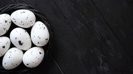 small group of animals : Whole Chicken eggs in a nest on a black rustic wooden background. Easter symbols or Healthy food concept. Stock Footage