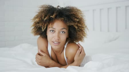 tisztaság : Portrait of adorable ethnic woman with curls bedding on comfortable bed and posing while looking at camera with wonderful smile. Stock mozgókép
