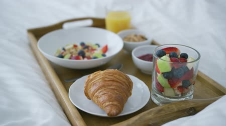 tray : Composed delicious fruit mix in glass and croissant with glass of juice for healthy and filling morning meal served on tray on bed. Stock Footage