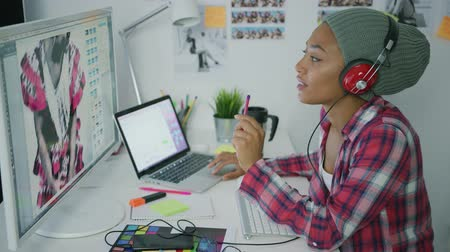 editor : Young ethnic woman wearing hat and listening to music with headphones posing at table in office working on new project and watching computer. Stock Footage