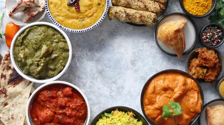 tikka : Assorted indian food on stone background. Dishes of indian cuisine. Tikka masala, butter chicken, Nilgiri, seekh kebab, rice, Onion Bhajia, paneer, samosa, naan, Daal Tarka, spices With copy space
