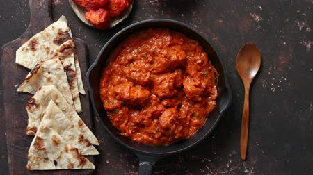 tikka : Traditional Indian chicken tikka masala spicy curry meat food in cast iron pan served with naan bread and spices. Flat lay. Top view.
