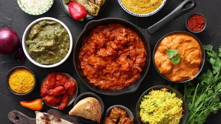 tikka masala : Various Indian dishes on a table. Spicy chicken Tikka Masala in iron pan. Served with rice, naan and spices. Set of different kind Indian food.