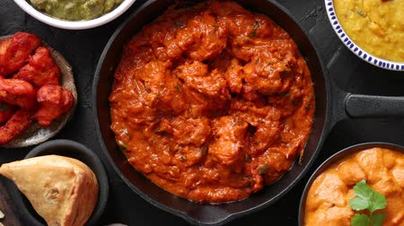 карри : Various Indian dishes on a table. Spicy chicken Tikka Masala in iron pan. Served with rice, naan and spices. Set of different kind Indian food.