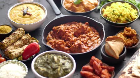 tikka : Various Indian dishes on a table. Spicy chicken Tikka Masala in iron pan. Served with rice, naan and spices. Set of different kind Indian food.
