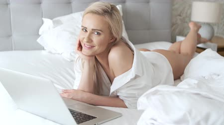 пуховое одеяло : A smiling blonde woman lying down the bed in front of her laptop with her legs raised slightly