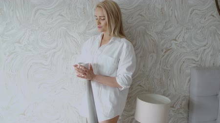 smell : Beautiful blonde woman standing next to a window in a loft apartment. Wearing men shirt and drinking coffee from a cup.