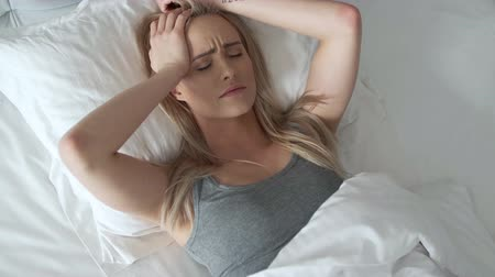 брюнет : Women sitting on bed holding her head. She has a painful headache with migraine.