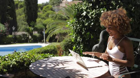 bord de piscine : Young ethnic woman in white swimming suit posing at table in garden of tropical resort and watching laptop in sunlight.