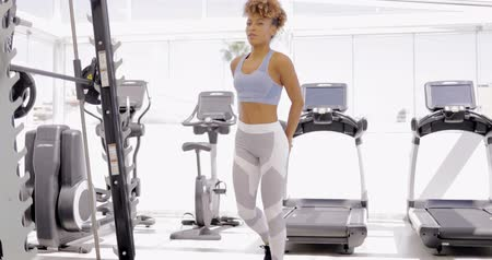 concentrar : Young ethnic woman wearing stylish sportive outfit and posing in modern light gym working with concentration looking forward. Vídeos